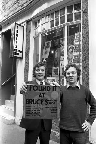 Owners Brian Findlay and Bruce Findlay with the distinctive red carrier bag 'I Found It At Bruce's' outside Bruce's record shop in Rose Street Edinburgh in November 1972